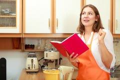 Casalinga con il libro di cucina in cucina Fotografie Stock Libere da Diritti