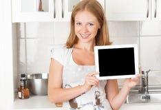 Casalinga della donna nella cucina con un computer vuoto in bianco della compressa immagini stock libere da diritti