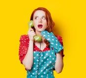 Casalinga della testarossa con il microtelefono del telefono di quadrante fotografie stock libere da diritti