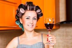 Casalinga di mezza età femminile nella cucina con bicchiere di vino Immagini Stock Libere da Diritti