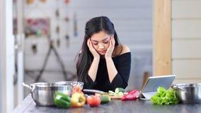 Casalinga femminile asiatica triste alla moda che cucina pasto fresco alla cucina che ha emicrania video d archivio