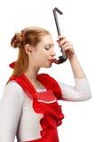 Casalinga graziosa in grembiule rosso con le code di cavallo divertenti che assaggiano pasto fotografia stock libera da diritti