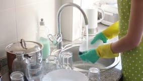casalinga in guanti di gomma che lava i piatti i stock footage