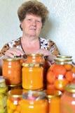Casalinga matura con le verdure inscatolate domestiche immagini stock libere da diritti