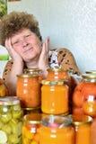 Casalinga matura con le verdure inscatolate domestiche fotografia stock