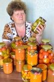 Casalinga matura con le verdure inscatolate domestiche Immagine Stock