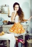 Casalinga pazza della donna vera sulla cucina, mangiante perfoming, bizare immagini stock