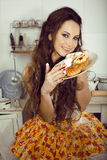 Casalinga pazza sulla cucina che sorride mangiando i dolci Fotografia Stock