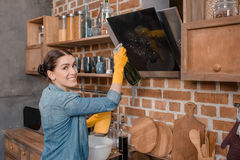 Casalinga sorridente in guanti di gomma che puliscono set televisivo a casa Fotografie Stock Libere da Diritti