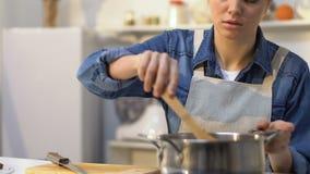 Casalinga stanca che aggiunge pomodoro tagliato nella pentola con salsa, routine di ogni giorno d'alesaggio stock footage
