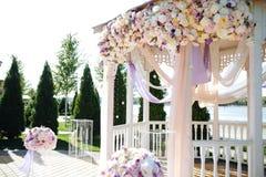 Casamento ao ar livre ceremony Arco do casamento Arco feito da madeira decorada com as flores pasteis de matéria têxtil de algodã imagem de stock
