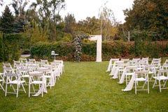 casamento ceremony Arco do casamento O arco do casamento feito dos ramos, das flores e das hortaliças está na grama verde no banc imagens de stock royalty free