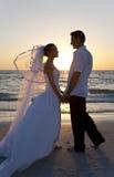 Casamento de praia do por do sol do casal da noiva & do noivo Fotos de Stock