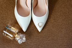casamento decor As sapatas da noiva, os perfumes e aliança de casamento bonita em um fundo marrom fotos de stock