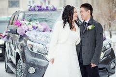 Casamento do inverno, o par feliz antes do carro decorado em uma rua nevado A noiva e o noivo olham se Imagens de Stock