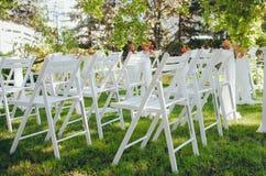 Casamento estabelecido Cerim?nia no peito da natureza Cadeiras brancas com as flores ajustadas na grama fotografia de stock royalty free