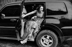 Casamento feliz, par novo feliz bonito dos noivos que levanta o cuidado perto do automóvel preto grande Carro preto da cor Foto de Stock Royalty Free