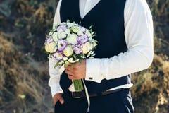 casamento O noivo em uma camisa branca e o waistcoat estão guardando ramalhetes das rosas brancas, hypericum, lisianthus, crisânt Imagens de Stock Royalty Free