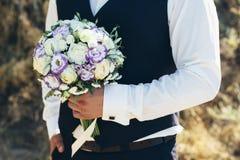 casamento O noivo em uma camisa branca e o waistcoat estão guardando ramalhetes das rosas brancas, hypericum, lisianthus, crisânt Imagem de Stock Royalty Free