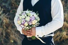 casamento O noivo em uma camisa branca e o waistcoat estão guardando ramalhetes das rosas brancas, hypericum, lisianthus, crisânt Imagem de Stock