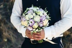 casamento O noivo em uma camisa branca e o waistcoat estão guardando ramalhetes das rosas brancas, hypericum, lisianthus, crisânt Fotos de Stock