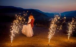 Casamento romântico disparado dos recém-casados de beijo O noivo está levantando acima da noiva nas montanhas decoradas com foto de stock