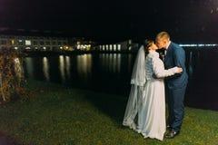 Casamento romântico Noivos que beijam perto do lago da noite iluminado com luz brilhante das janelas do salão do banquete Imagens de Stock