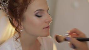 Casandose al artista de maquillaje que hace para compensar a la novia en velo Modelo atractivo hermoso almacen de metraje de vídeo