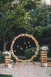 Casandose el arco redondo en estilo rústico adornado con la hierba haga heno el color de campo y las bombillas retras Cerca de la Foto de archivo