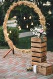 Casandose el arco redondo en estilo rústico adornado con la hierba haga heno el color de campo y las bombillas retras Cerca de la Fotos de archivo