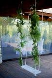 Casandose el oscilación adornado con las flores que cuelgan en las ramas del sauce Imagen de archivo libre de regalías