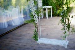 Casandose el oscilación adornado con las flores que cuelgan en las ramas del sauce Imágenes de archivo libres de regalías