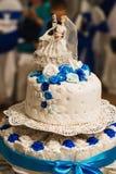 Casandose la torta blanca adornó con las rosas con tres gradas una figura de la novia y del novio Fotografía de archivo libre de regalías
