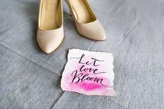 Casandose los zapatos blancos y frase romántica - deje la floración del amor Imagen de archivo