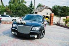 Casandose negro adornado con el coche lujoso de las flores que llega con Fotos de archivo