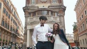 Casandose pares camina en la calle de la ciudad en Roma, Italia El novio elegante da la chaqueta para calentar a su novia hermosa metrajes