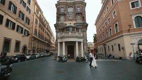 Casandose pares camina en la calle de la ciudad en Roma, Italia Novio elegante y novia hermosa en el paseo Luna de miel en Italia almacen de metraje de vídeo