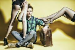 年轻casanova人与suitcasen amd女性腿 免版税库存照片