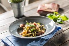 Casarecce della pasta con il parmigiano del pancetta del bacon ed il basilico delle erbe Cucina italiana o mediterranea fotografie stock
