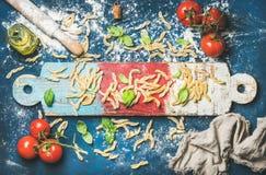 Casarecce, pomodori ciliegia, foglie del basilico e olio d'oliva italiani a bordo fotografia stock