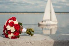 Casarse el ramo nupcial con el res y las rosas blancas contra la perspectiva del theyacht Concepto de la boda Foto de archivo