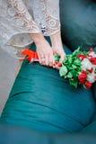 Casarse el ramo nupcial con las rosas blancas y rojas en sus manos en fondo azul Imagen de archivo