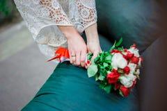 Casarse el ramo nupcial con las rosas blancas y rojas en sus manos en fondo azul Imágenes de archivo libres de regalías