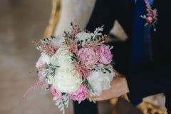 Casarse el ramo rosado en las manos del novio foto de archivo