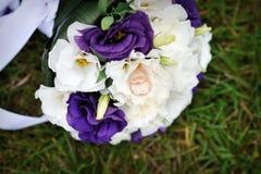 Casarse el ramo y los anillos púrpuras Imagen de archivo