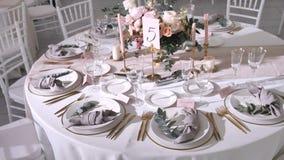 Casarse las decoraciones de la tabla para las huéspedes en estilo moderno, el centro de flores con las rosas y el eucalipto, colo almacen de video