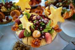 Casarse las diversas frutas frescas y bayas con color sabroso en una tabla de comida fría, estrella con la piña Foto de archivo