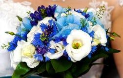 Casarse las flores azules y blancas en manos de la novia en día de boda Fotografía de archivo