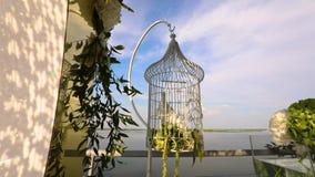 Casarse las palomas que se sientan en una jaula, una paloma blanca que se sienta en jaula en el fondo del río y un cielo azul, di almacen de metraje de vídeo
