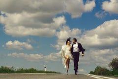 casarse los pares felices que corren en el camino imagen de archivo libre de regalías